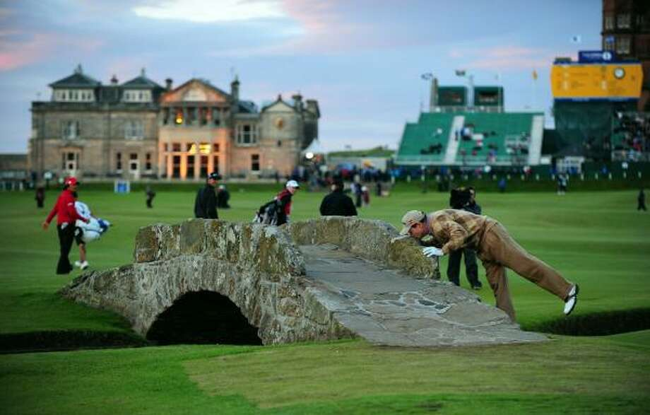 US golfer Tom Watson kisses the Swilcan Bridge in front of the clubhouse on the 18th hole. Watson's 4 over par total will mean he misses the cut, so this will be his last appearance in an Open Championship at St Andrews. Photo: ADRIAN DENNIS, AFP/Getty Images