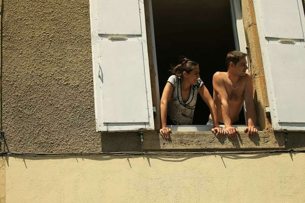 A couple watches as the peloton travels through rural France.