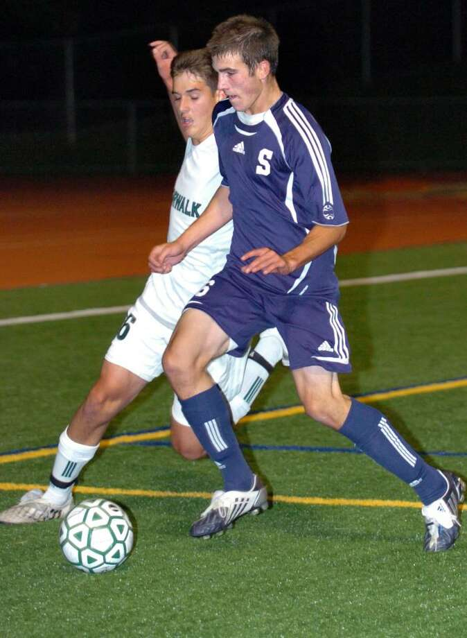 Norwalk's Sean Whitteaker, left, and Staples' Sean Gallagher battle for control of the ball during the first half of Tuesday night's game in Norwalk. Photo: Autumn Driscoll / Connecticut Post
