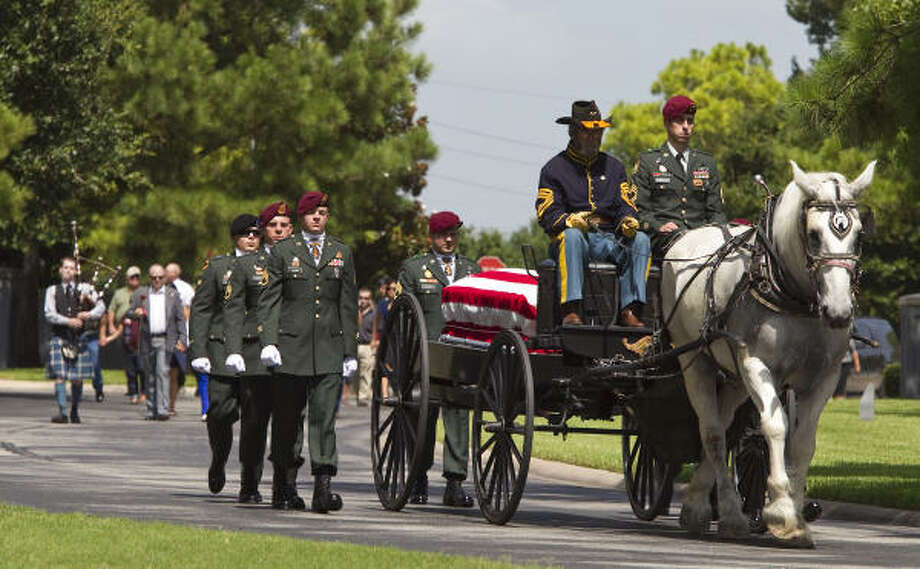 Jim Booth drives a french draft horse with a cassion carrying the casket of Army Sgt. Andrew Creighton who died in Afghanistan. Photo: Nick De La Torre, Chronicle
