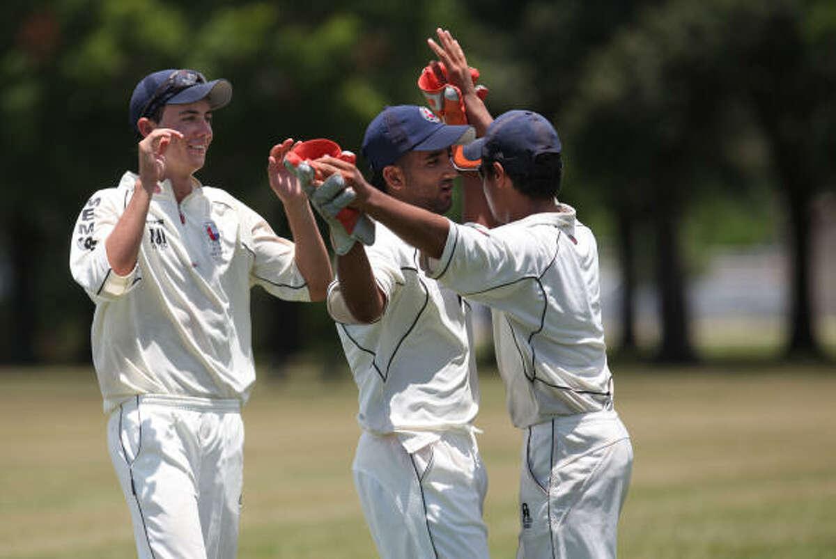 Ryan Corns, left, Iftikhar Ahmed, center, and Shujah Naqui, all members of the Memorial Nationals Cricket Club, celebrate getting Jam Niaz, a member of the Houston Cougars Cricket Club, out of the game.