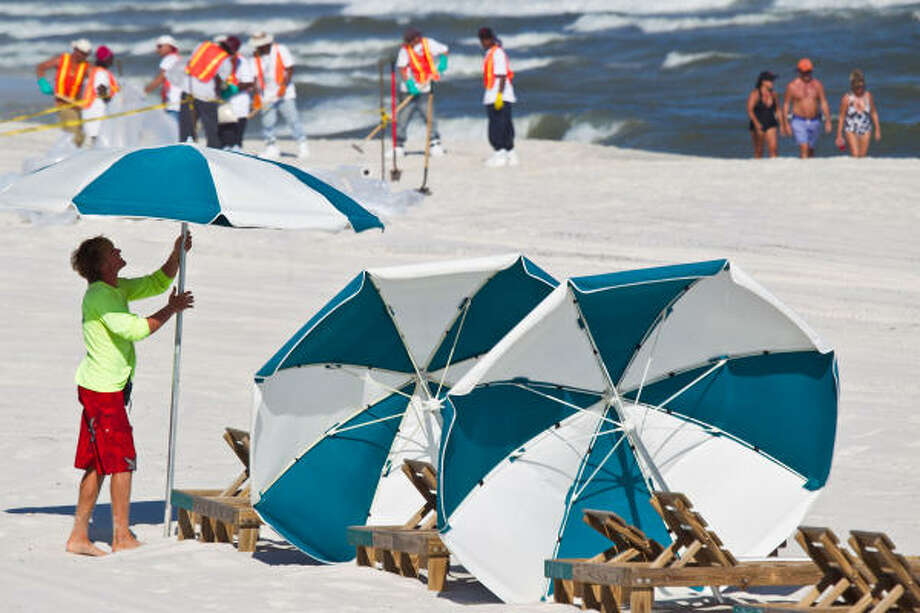 Beach regulars said the normally busy holiday weekend looked more like 'snowbird season.'   Honeycutt works the beach in the summers to pay for college. Photo: Smiley N. Pool, Chronicle
