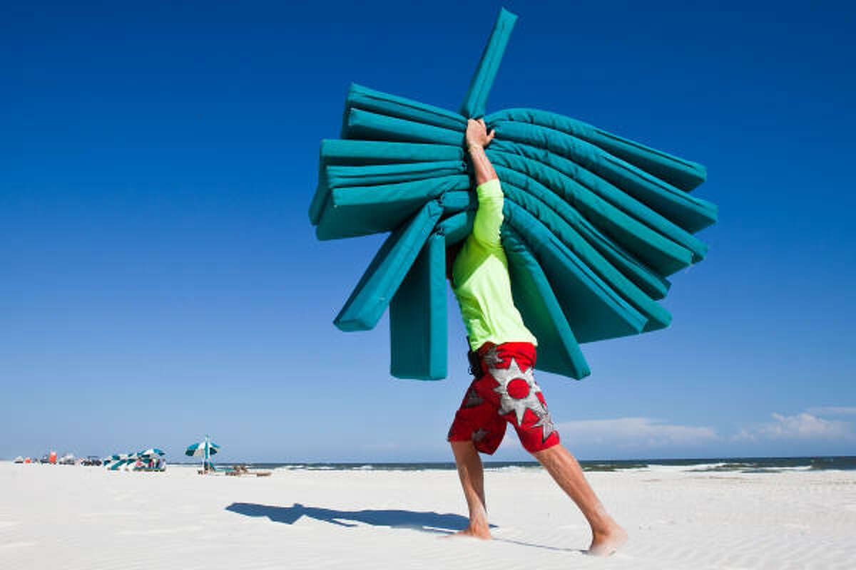 Beach attendant Hampton Honeycutt, 21, of Perdido Beach Services, puts away unused lounge cushions and beach umbrellas in Orange Beach, Ala. Business on the beach was off by at least 70 percent from what it was the previous Independence Day weekend Honeycutt said.