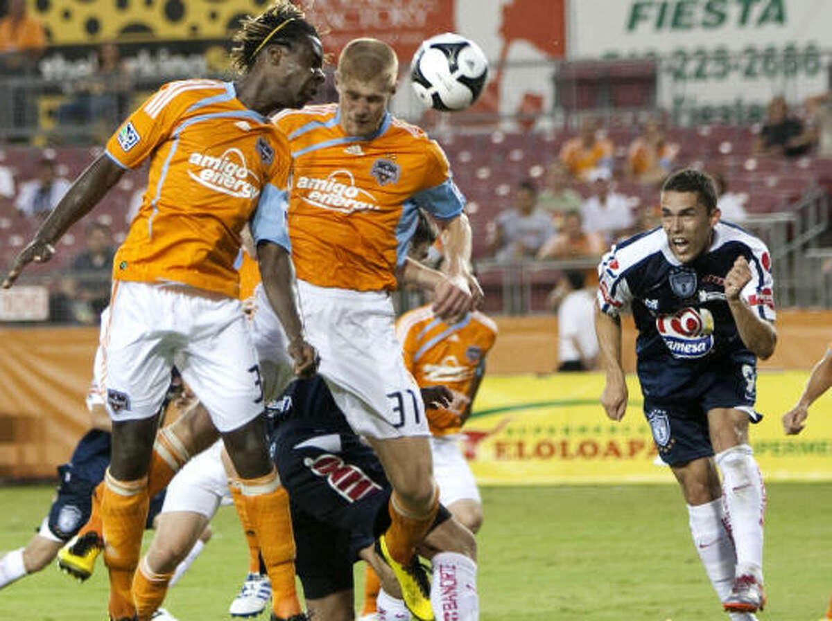 Dynamo forward Joseph Ngwenya, left, and defender Andrew Hainault go for a header in the box against Pachuca's Herculez Gomez during the second half of their SuperLiga 2010 group play opener Thursday night at Robertson Stadium. Ngwenya scored a pair of goals to lead the Dynamo to a 2-1 win.