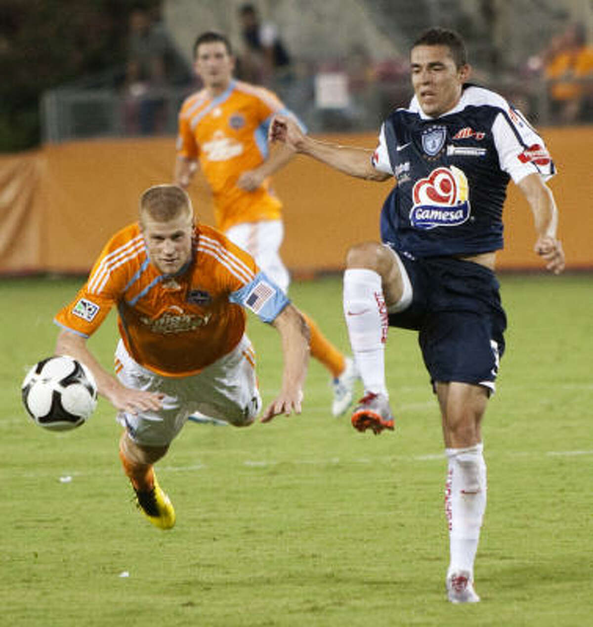 Dynamo forward Andrew Hainault heads the ball forward as he dives past Pachuca's Herculez Gomez during the second half.