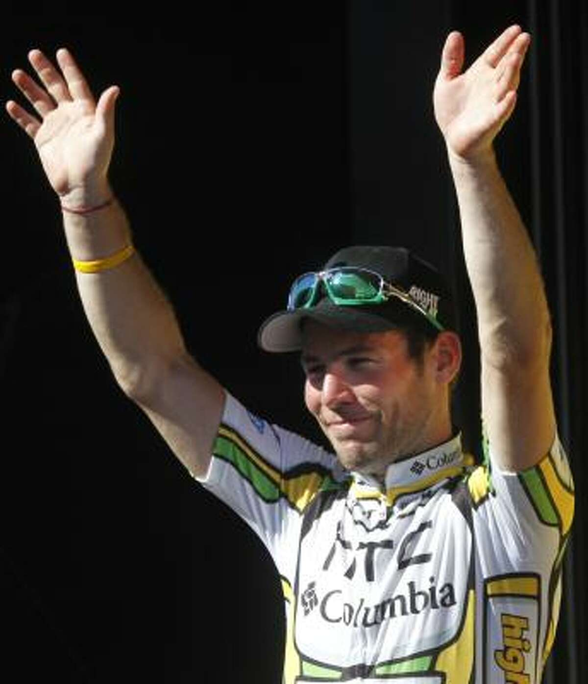 Mark Cavendish greets spectators on the podium after his win in the 11th stage.