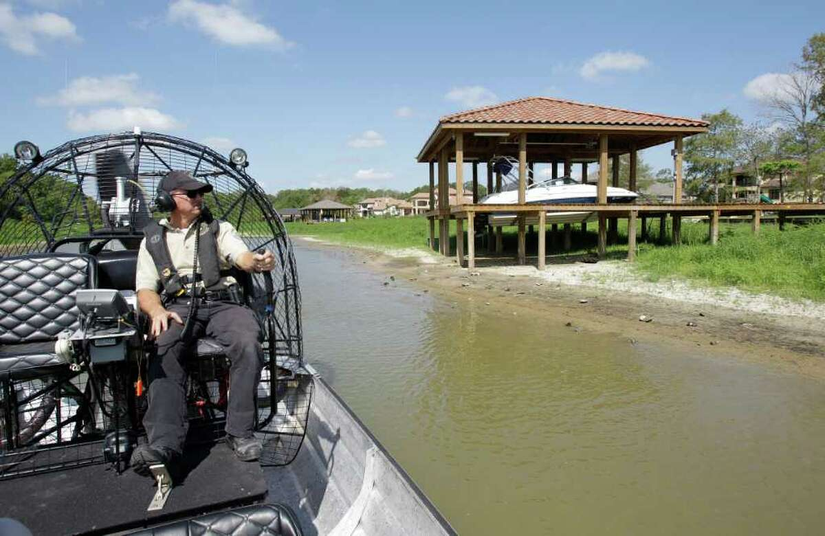 Texas Game Warden, Kevin Creed, patrols in an airboat past boats in landlocked boathouses on Lake Houston Wednesday, Aug. 3, 2011. The drought has caused the lake level to drop nearly seven feet. Many of the lakefront homes along Lake Houston now have landlocked boathouses and their waterfront view is now father away. ( Melissa Phillip / Houston Chronicle )
