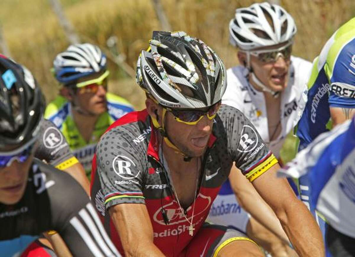 Lance Armstrong, center, grimaces as he rides in the pack during Stage 10 of the Tour de France.