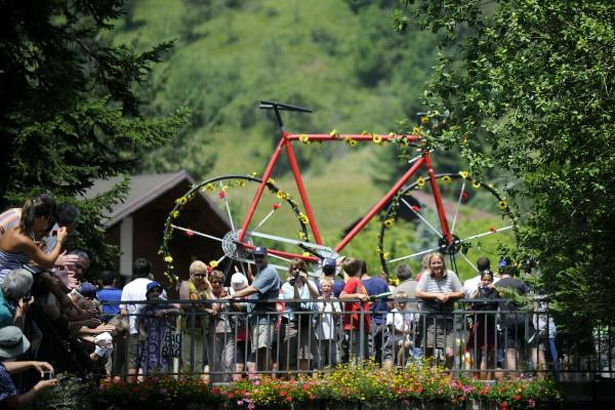 Fans wait for riders near a huge bike decoration.