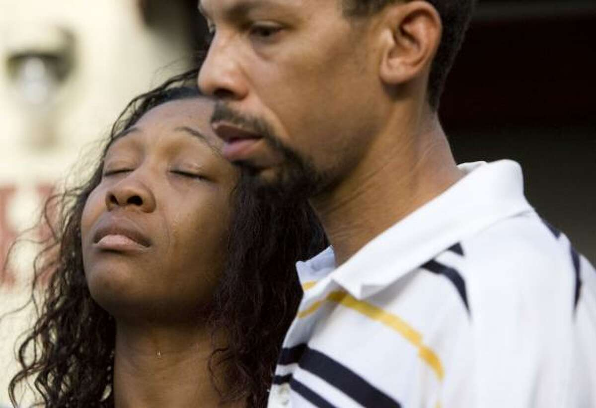 During a prayer vigil to honor the memory of her 6-year-old son Tekerrious Jackson, Lucy Adams cries along side her husband Emiel Adams as they are surrounded by family and well wishers at the site of the small apartment complex in Houston where her son Tekerrious Jackson was allegedly beaten to death by his father, Alex Duncan McGowen.