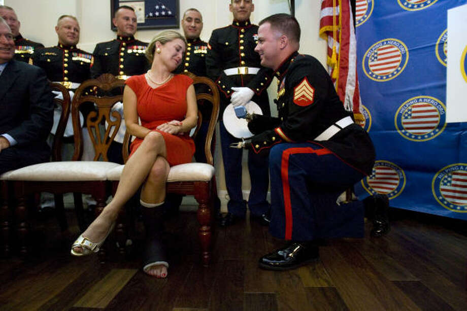 "U.S. Marine Sgt. James ""Eddie"" Wright proposes to his girlfriend Cody Fife after he received a new home through Helping A Hero.Org and Semper Fi Fund organizations in Conroe.  Sgt. Wright was awarded the Bronze Star for his actions after his Bravo Company 1st Recon platoon was ambushed in Fallujah, Iraq in 2004. A rocket propelled grenade blew off his forearms and hands and caused his femur on his left leg to be fractured. Sgt. Wright led his team to safety while directing his Marines, resulting in 26 enemy kills while dealing with his own injuries. Photo: Johnny Hanson, Houston Chronicle"