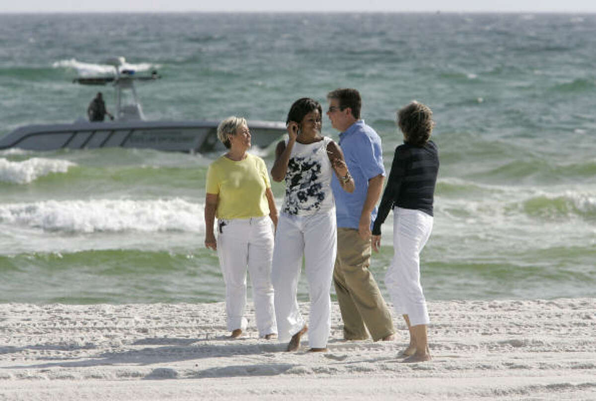First lady Michelle Obama walks barefoot on the beach at the Boardwalk Beach Resort on Panama City Beach, Fla, on Monday, July 12, 2010. She is accompanied by, left to right, Panama City Beach Mayor Gayle Oberst, Dan Rowe, Bay County Tourist Development Council, and Carol Browner, U.S Department of Commerce.
