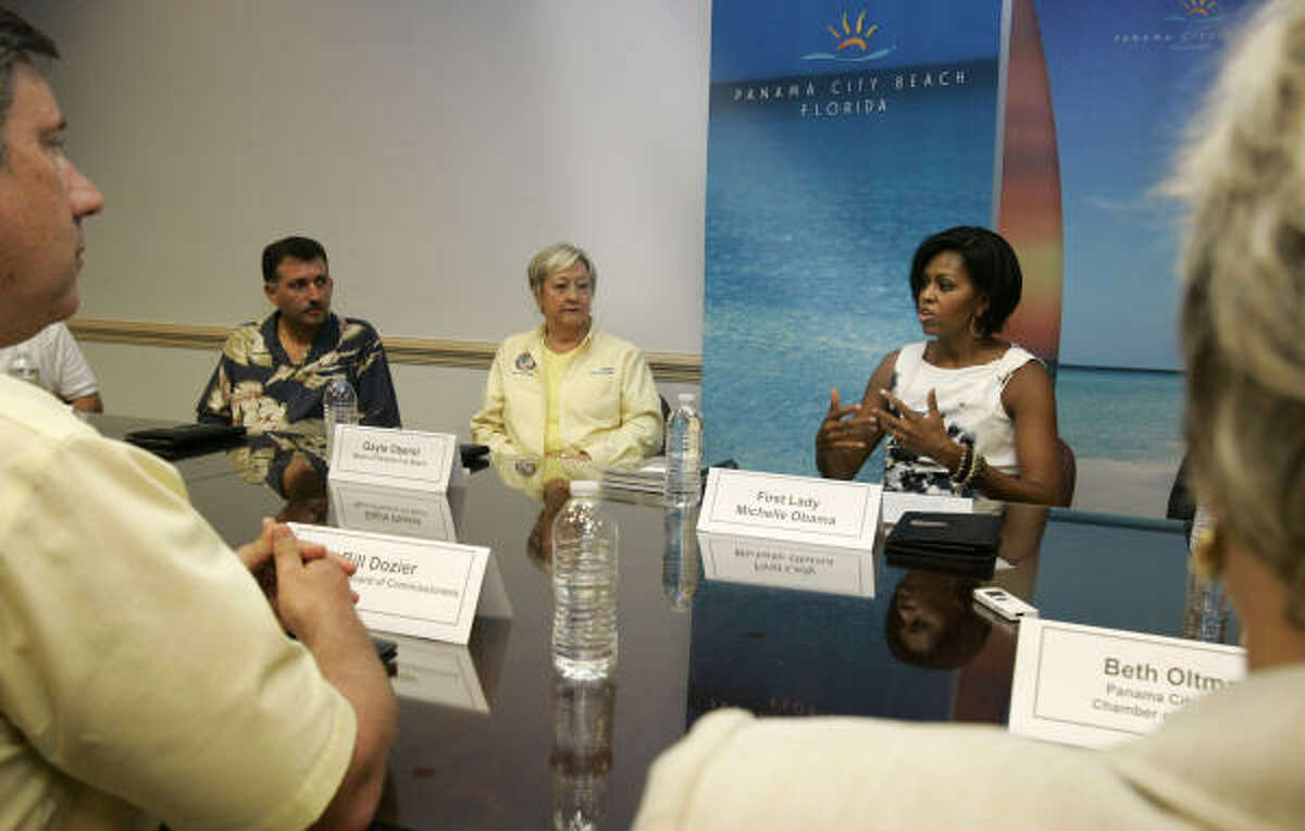First lady Michelle Obama speaks during a roundtable discussion at the Panama City Beach Welcome Center in Panama City Beach, Fla., Monday, July 12, 2010. Yonnie Patronis, owner of Capt. Anderson's Restaurant, left, and Panama City Beach Mayor Gayle Oberst, center look on.