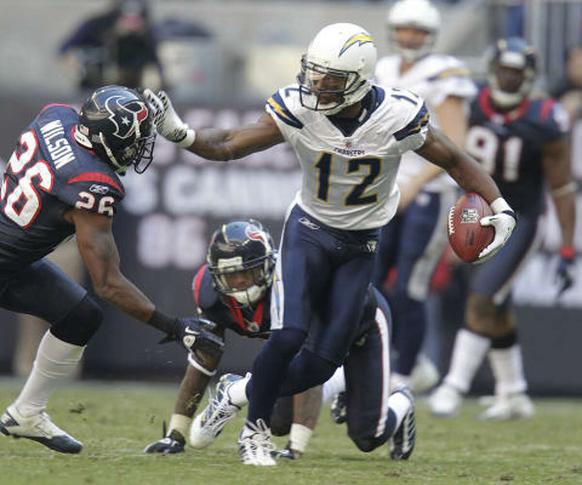 Texans cornerback Kareem Jackson, rear, gets burned while trying to tackle Chargers wide receiver Patrick Crayton (12), as Texans safety Eugene Wilson comes in to try to stop him during the third quarter.