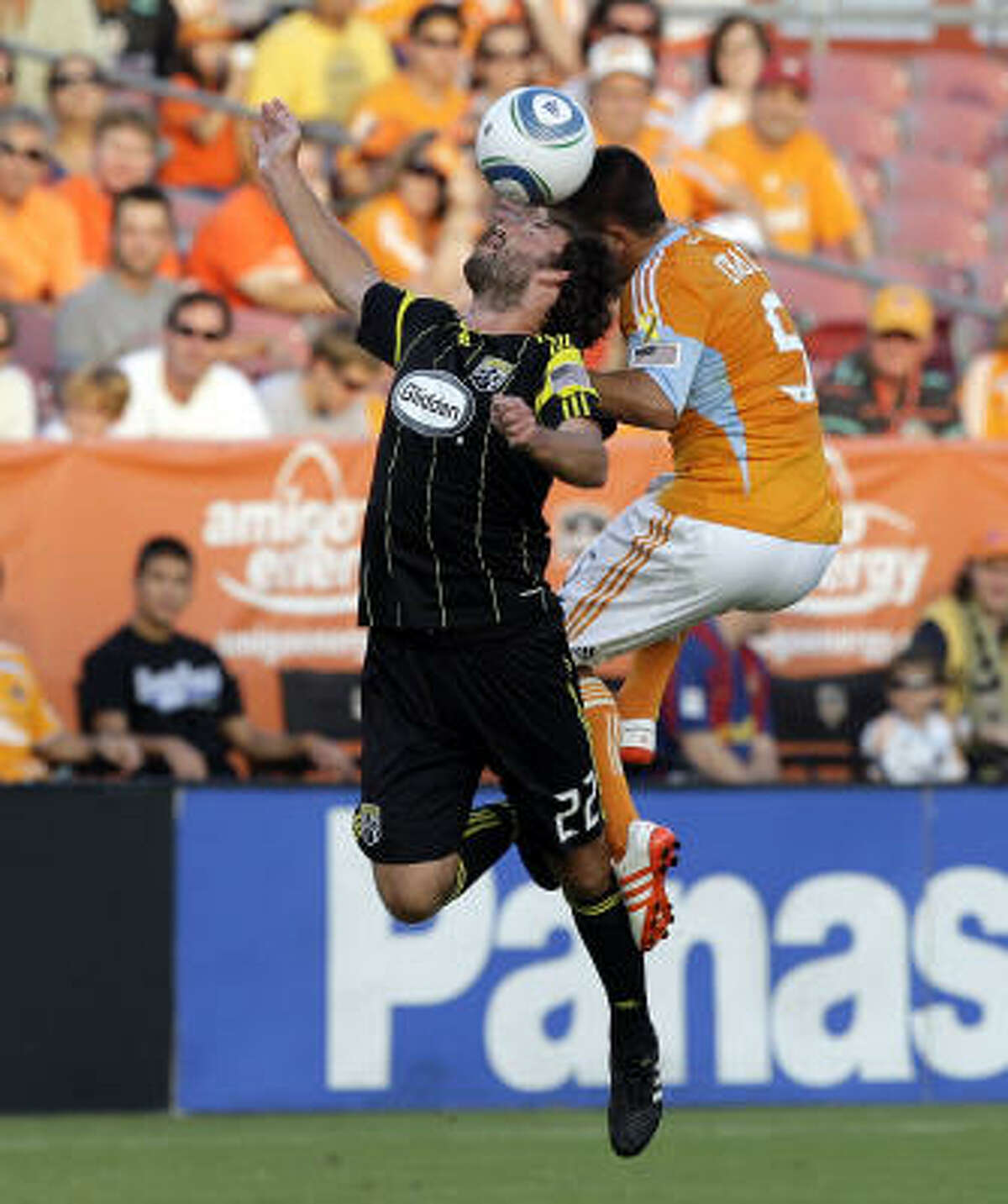 Columbus' Adam Moffat, left, and Dynamo midfielder Danny Cruz battle for possession of the ball in the first half.