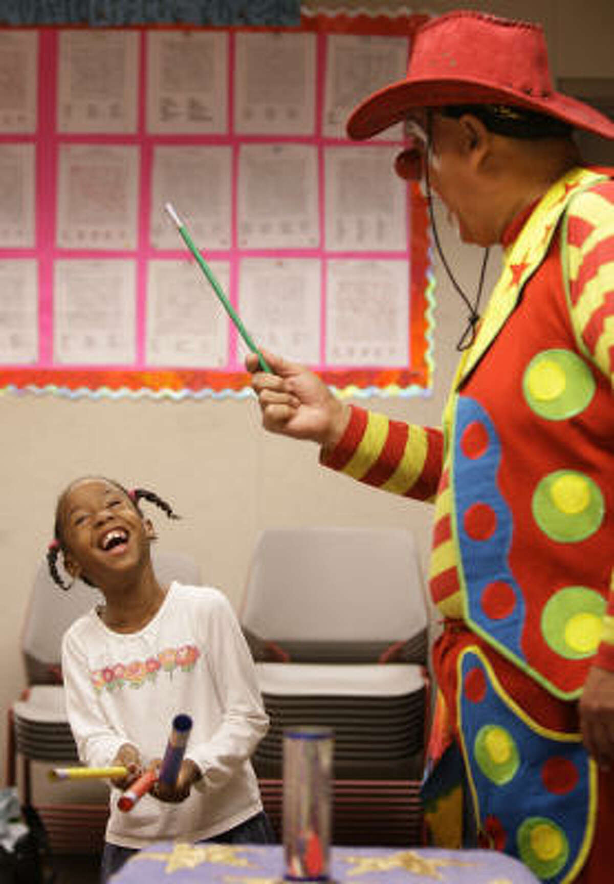 Dominique Bufkin-Lewis, 6, laughs as she assists Happy the Clown performed by Ruben Ramirez during program at Walter Neighbor Library in Houston. Programs for all ages such as science, crafts, games, and entertainers are offered throughout the summer as part of the 2010 Summer Reading Program at the Houston Public Libraries.