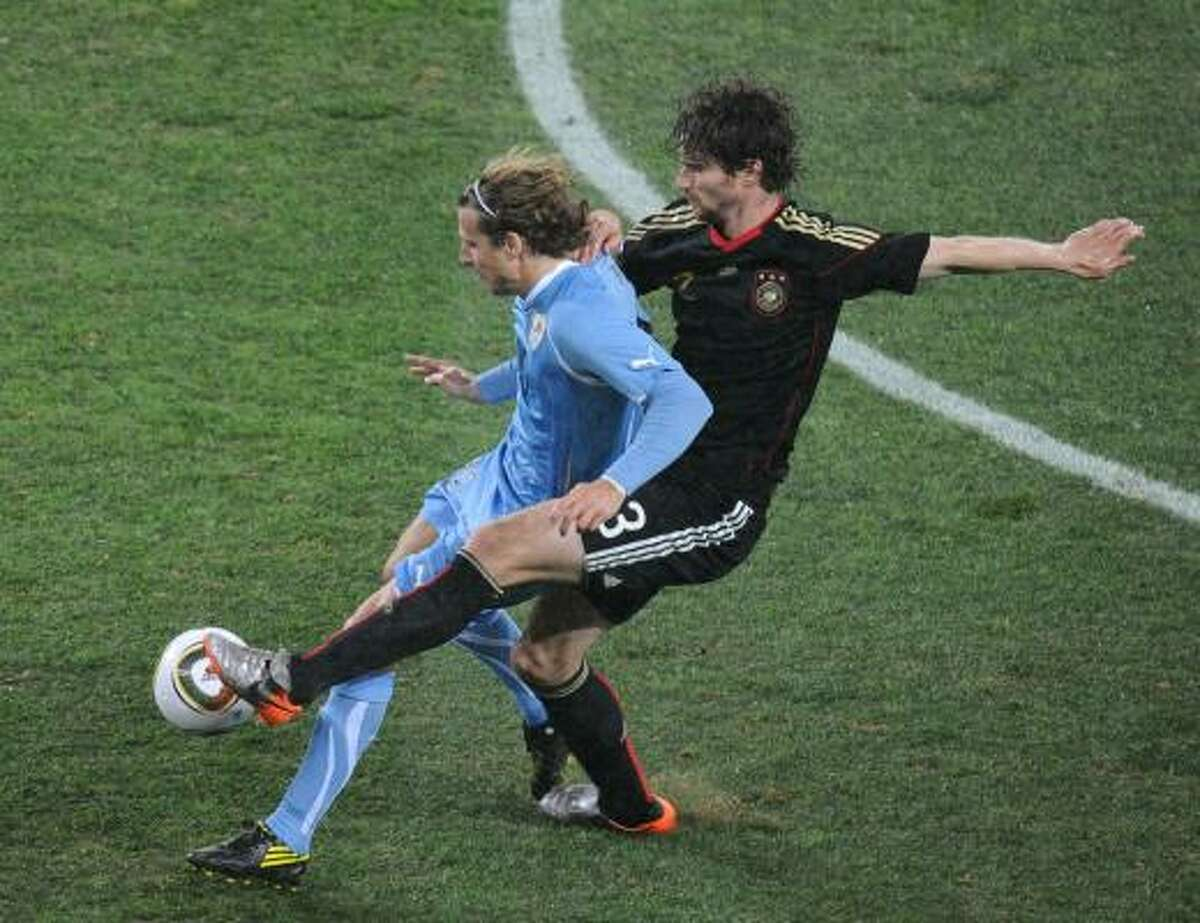 Uruguay striker Diego Forlan, left, and Germany's defender Arne Friedrich fight for possession.
