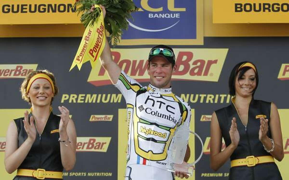 Stage winner Mark Cavendish celebrates on the podium.