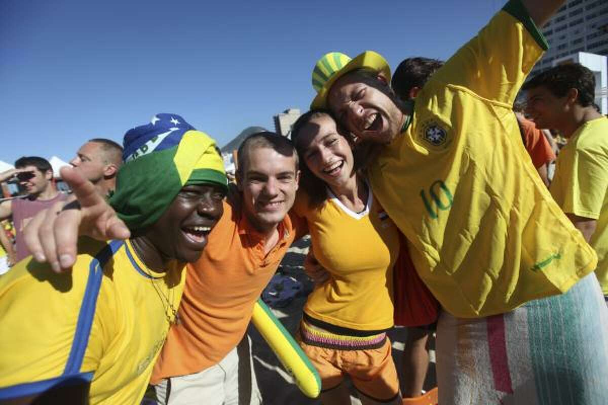Fans of Brazil and Netherlands soccer teams party together at Copacabana Beach in Rio de Janeiro.