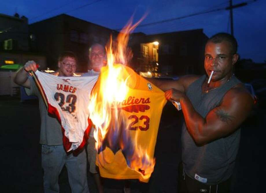 (From left) Cleveland Cavaliers fans Josh Hall, Rob Hose and Mike Adams set fire to LeBron James jerseys Thursday night in Akron, Ohio after James announced that he was leaving the Cavaliers after seven seasons to sign with the Miami Heat. Photo: Phil Masturzo, AP