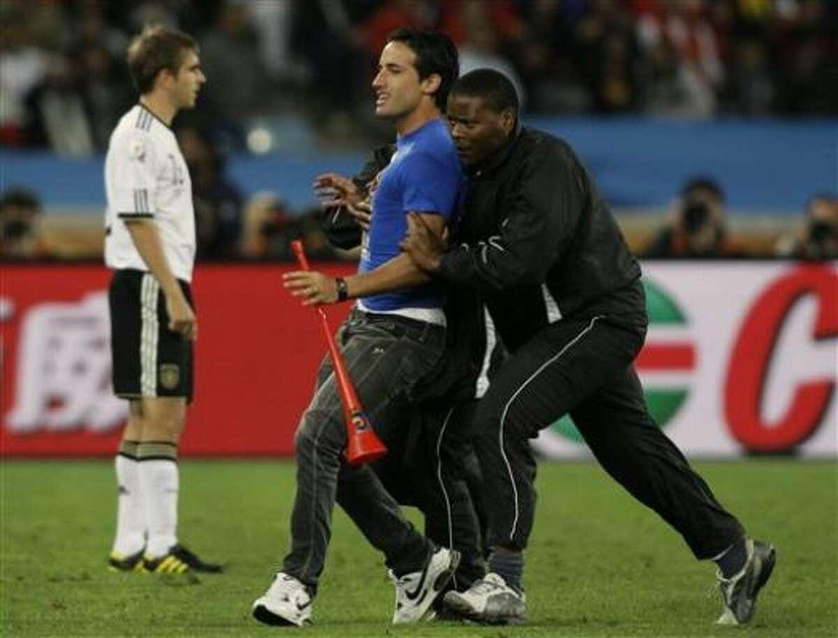 Un hombre no identificado, centro, es detenido por la seguridad después de entrar a la cancha durante el partido entre España y Alemania.