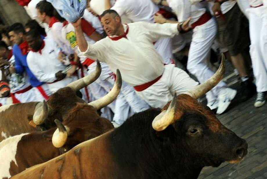 Participants run in front of Penajara Ranch fighting bulls on the first San Fermin Festival bull run, on July 07, 2010, in Pamplona, Spain. The festival is a symbol of Spanish culture, despite heavy condemnation from animal rights groups, and attracts thousands of tourists to watch the bull runs. Photo: ANDER GILLENEA, AFP/Getty Images
