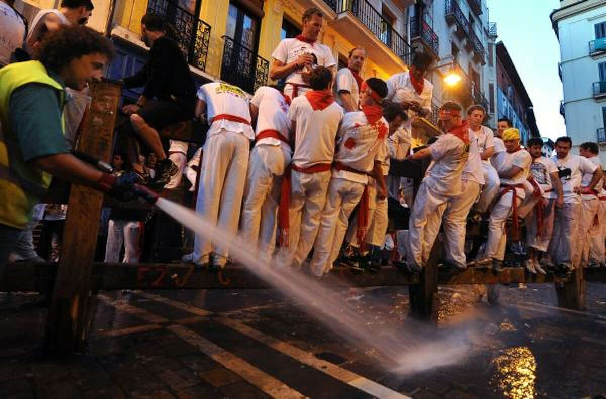 A worker hoses down the streets before the first bull run of the San Fermin Fiesta on July 7, 2010, in Pamplona, Spain.