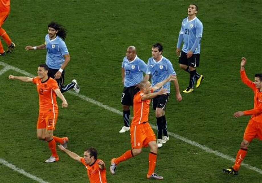 Netherlands' players celebrate their narrow win over Uruguay that put the Dutch in the final for the first time in 32 years. Photo: Eugene Hoshiko, AP