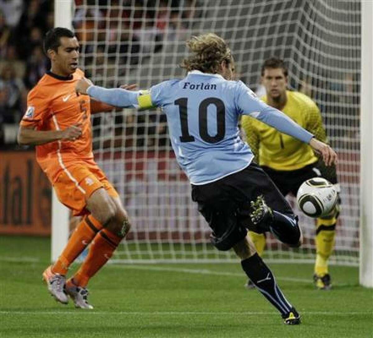 El jugador de Uruguay Diego Forlán, centro, remata al arco en el partido de semifinales de la Copa del Mundo contra Holanda, el martes 6 de julio de 2010, en el estadio Green Point de Ciudad del Cabo, Sudáfrica.