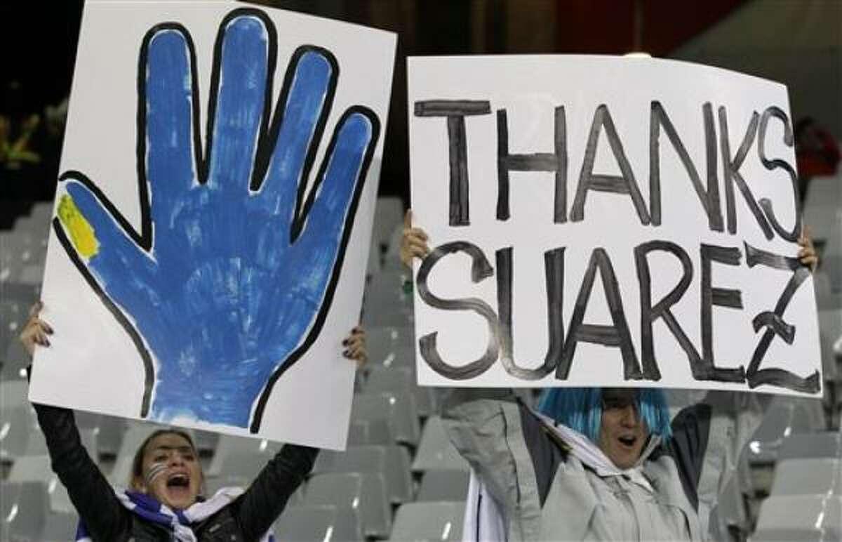 Hinchas uruguayos muestran carteles agradeciendo al jugador de Uruguay, Luis Suárez, quien detuvo con la mano un gol de Ghana en el partido por los cuartos de final contra Ghana. Los hinchas acudieron al partido contra Holanda por las semifinales del Mundial el martes, 6 de julio de 2010, en Ciudad del Cabo.