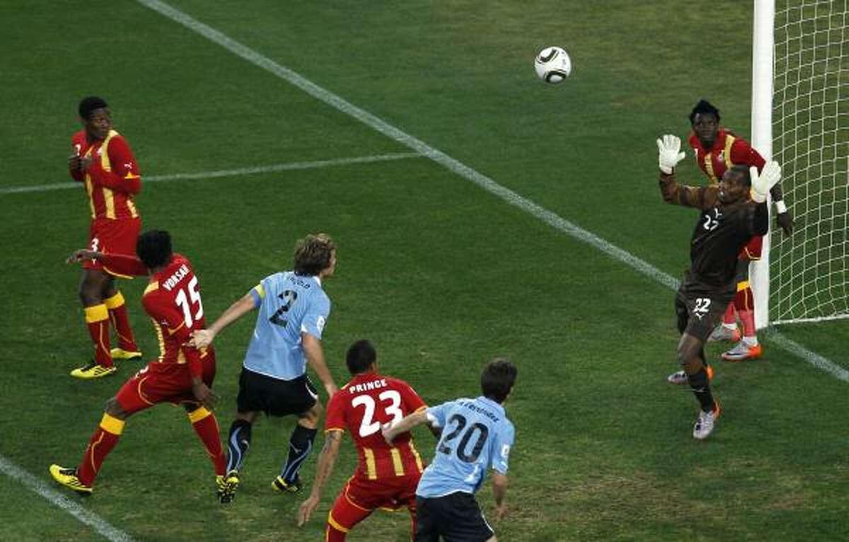 El arquero de Ghana, Richard Kingson, rechaza un cabezazo de Diego Lugano en el estadio Soccer City de Johannesburgo.