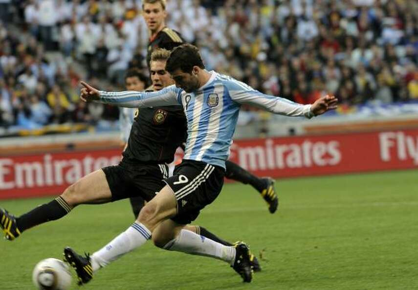 Germany defender Philipp Lahm, rear, fights for the ball with Argentina striker Gonzalo Higuain.