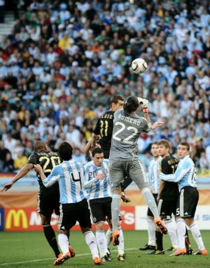Argentina goalkeeper Sergio Romero clears the ball away from Germany striker Miroslav Klose. Photo: JEWEL SAMAD, AFP/Getty Images