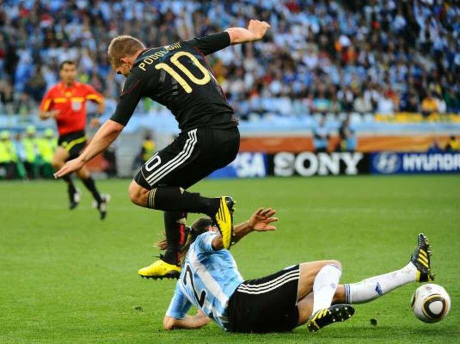 Germany striker Lukas Podolski jumps over Argentina defender Martin Demichelis. Photo: FRANCOIS-XAVIER MARIT, AFP/Getty Images