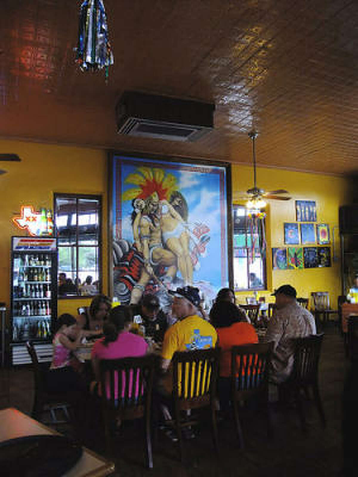 One of 2 scantily clad Aztec maiden-and-warrior paintings anchors the front of the dining room at Taco Haven's South Presa location.