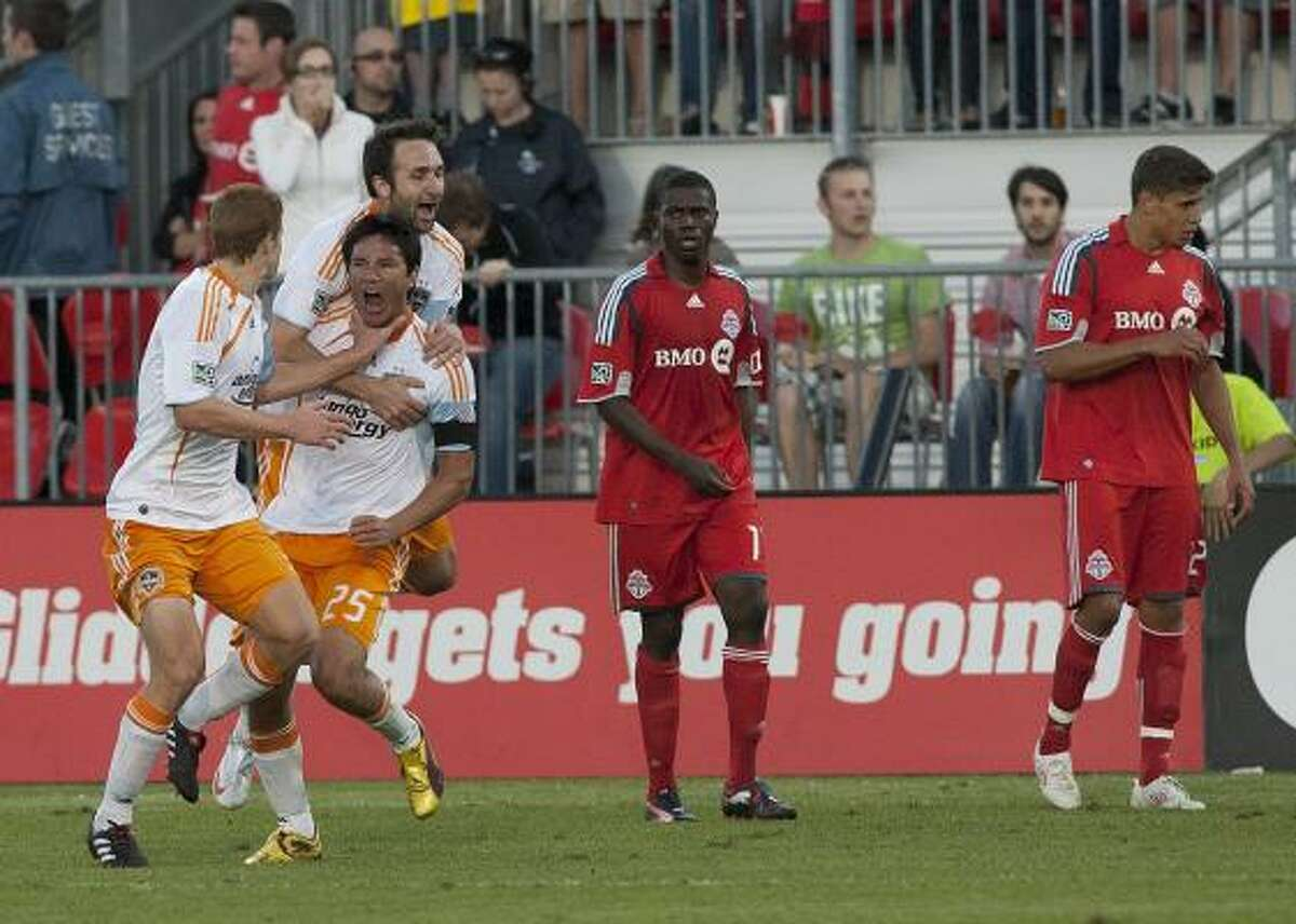 Dynamo's Brian Ching (25) celebrates scoring a goal with teammates Bobby Boswell, left, and Ryan Cochrane as Toronto FC's O'Brian White, center, and Adrian Cann, right, look on.