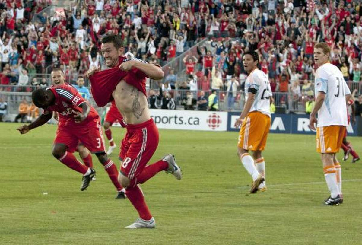 Toronto FC's Dan Garcia, foreground, celebrates after scoring his team's equalizer against the Dynamo during the second half.