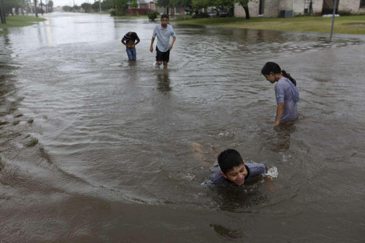 Un puñado de niños juega en el agua tras las fuertes lluvias que trajo Alex a Brownsville el miércoles por la noche.