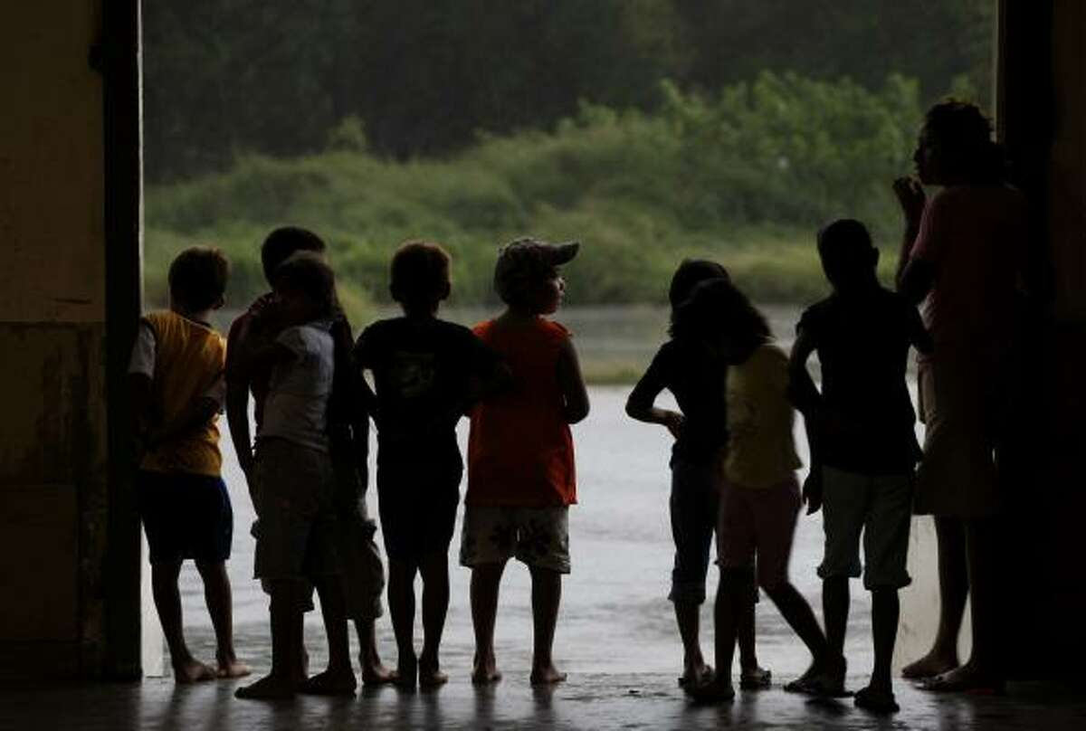 Niños refugiados por el huracán Alex miran desde el interior del centro de convenciones donde encontraron ayuda ante la primera tormenta en el Atlántico de esta temporada.