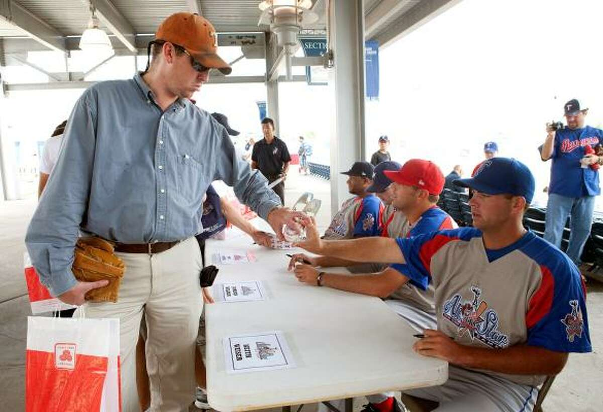Timothy Hale, left, retrieves his ball from Tulsa Drillers pitcher Keith Weiser during an autograph signing session at the 74th Annual Texas League All-Star game.
