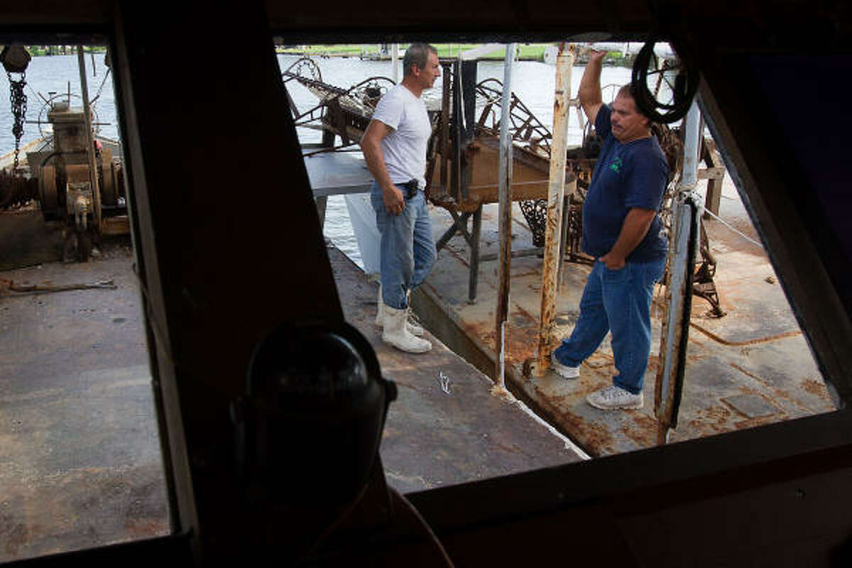 Oysterman Mark Naquin, left, and his cousin Dale Chaisson chat on Naquin's idle boats.