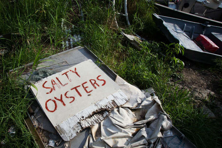 A sign sits collecting weeds at the buiness of oysterman Mark Naquin.  Naquin has seen his business halted since the Deepwater Horizon spill. Photo: Smiley N. Pool, Chronicle