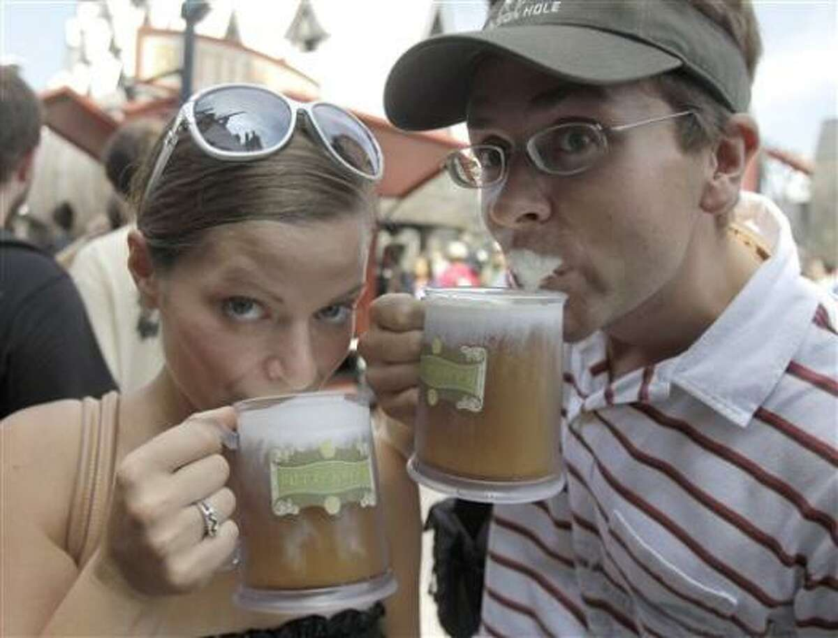 Park guests Jillian Woodworth, left, and Steven Hopke try Butterbeer at the grand opening of the Wizarding World of Harry Potter at Universal Orlando theme park in Orlando, Fla.