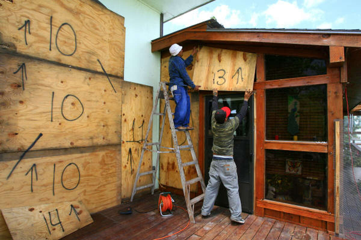 Norecio Salazar and Leonardo Salinas place a sheet of designated plywood over a window on Jim and JoAnne Farber's home on the Delta Lake Reservoir in preparation for Alex on Tuesday in Hidalgo County.