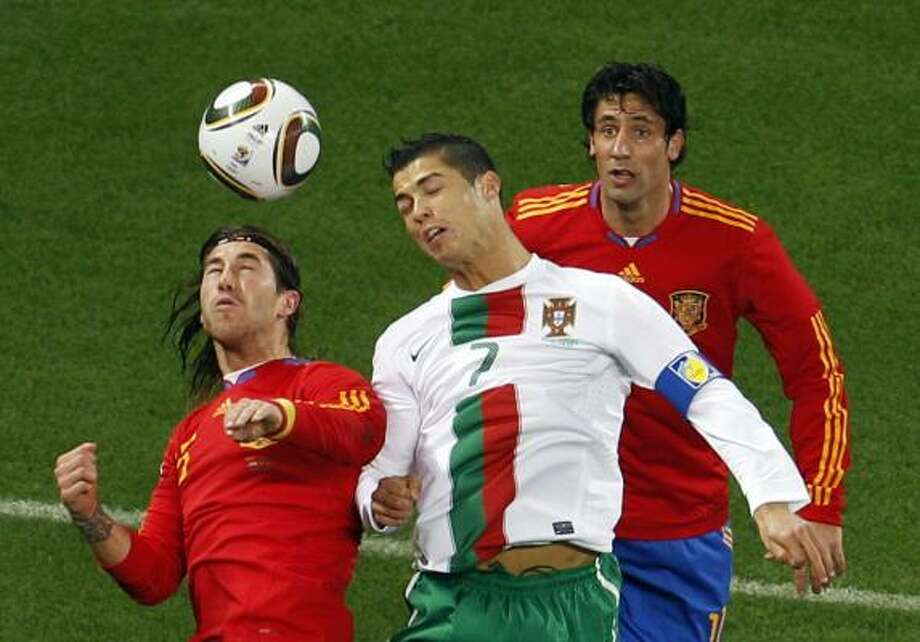 SPAIN 1, PORTUGAL 0 Portugal's Cristiano Ronaldo, center, heads the ball ahead of Spain's Sergio Ramos, left, and Joan Capdevila at Green Point stadium in Cape Town. Photo: Roberto Candia, AP