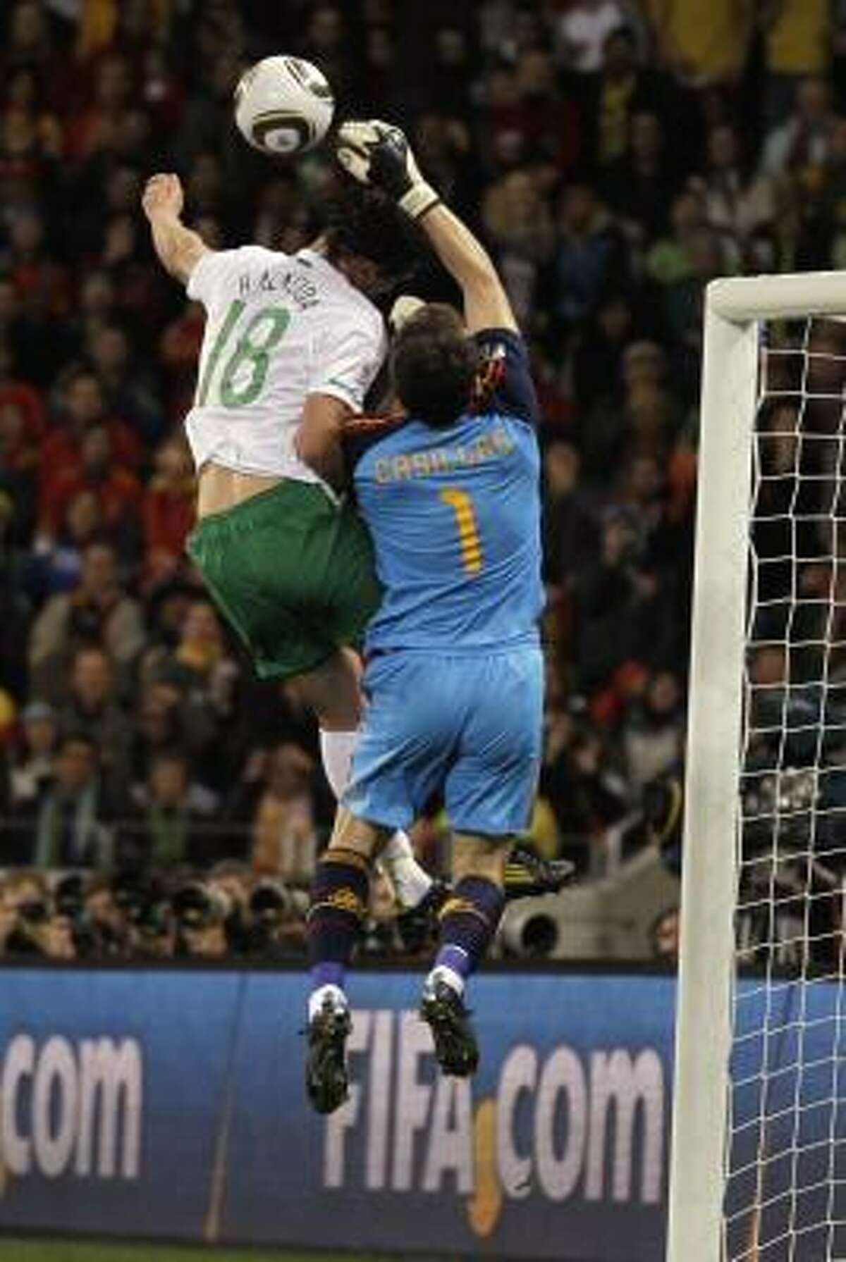 Spain goalkeeper Iker Casillas, right, punches away the ball from Portugal's Hugo Almeida.