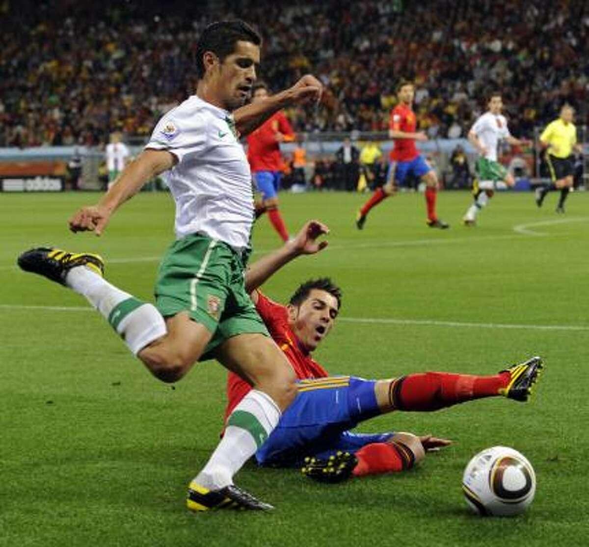 Portugal's Ricardo Costa goes to kick the ball as Spain's David Villa tries to block him.