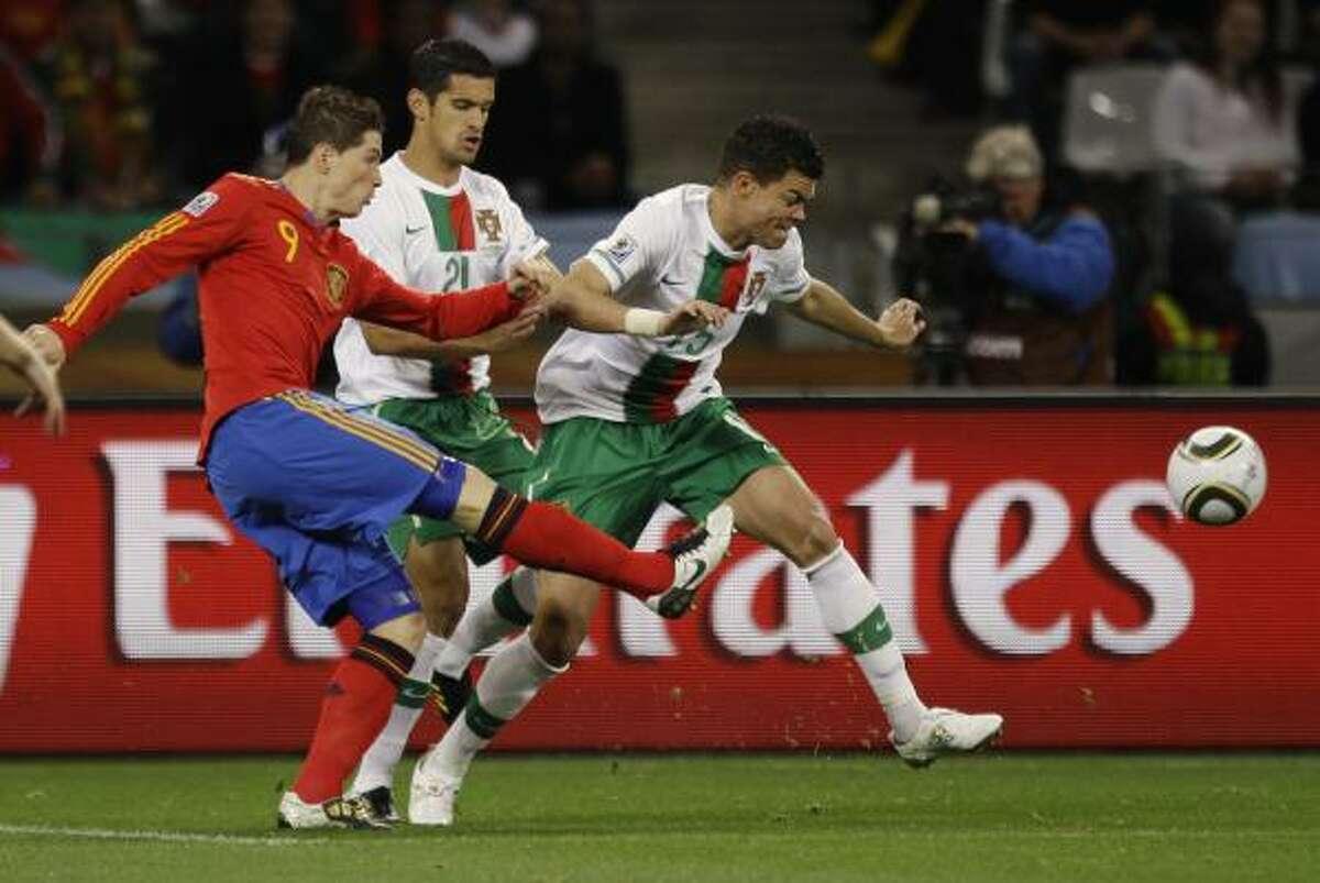 El delantero español Fernando Torres (izq.) tira ante la marca del portugués Ricardo Costa.