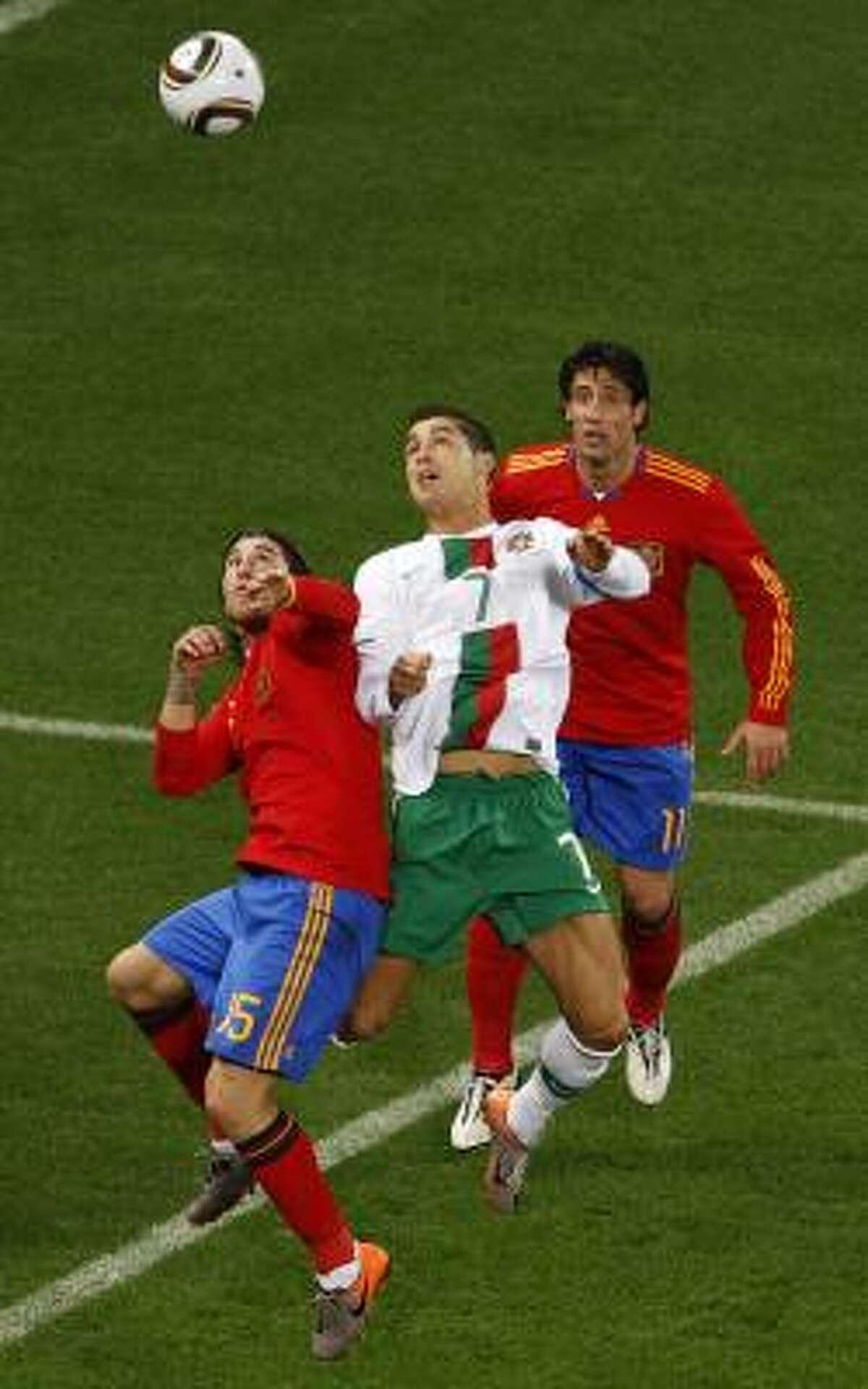 El portugués Cristiano Ronaldo (centro) salta entre los españoles Sergio Ramos y Joan Capdevila.