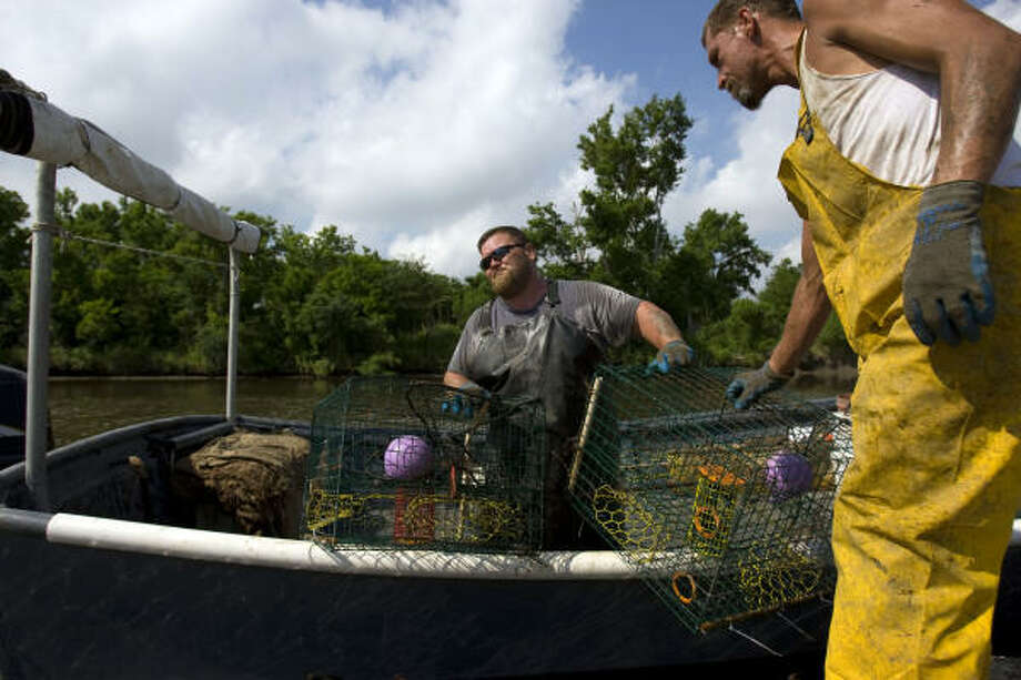 Chad Strange, (left) a fourth-generation fisherman, is helped by deckhand Robert Lewis in Hopedale, La. Without crabs to sell, Strange says, he has enough cash to last two weeks. Photo: Johnny Hanson, Chronicle